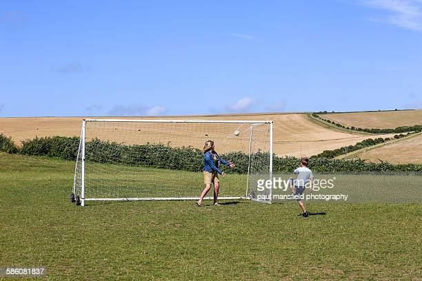 Mother and son playing football