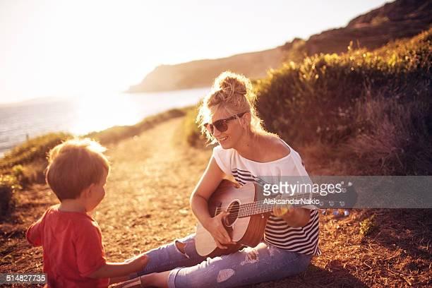 Mère et fils jouant de la guitare sur la plage
