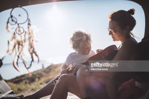 Mother and son playing guitar on the road trip