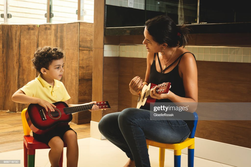 Mother and son playing guitar together : Stock Photo