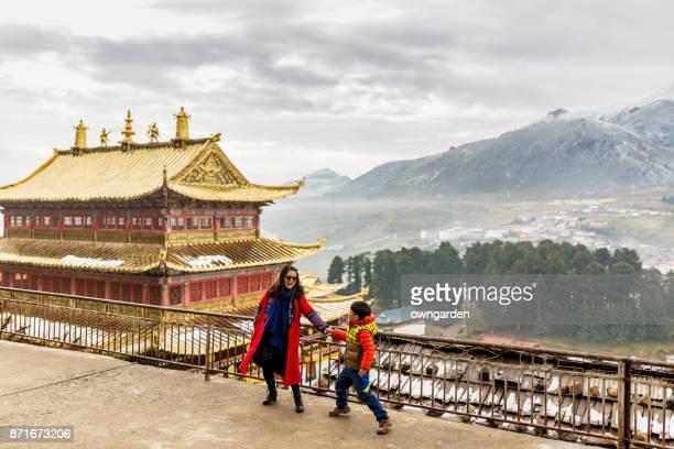 Madre e hijo jugando delante de templo Langmu