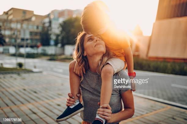 mãe e filho brincando em parque público, dirigindo scateboard - carinhoso - fotografias e filmes do acervo