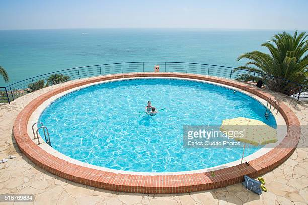 Mother and son playing inside circular pool with stunning view, Peñiscola, Spain