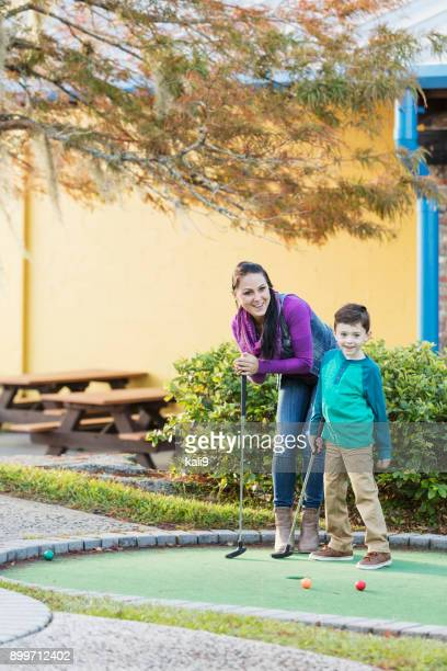 Mother and son playing miniature golf
