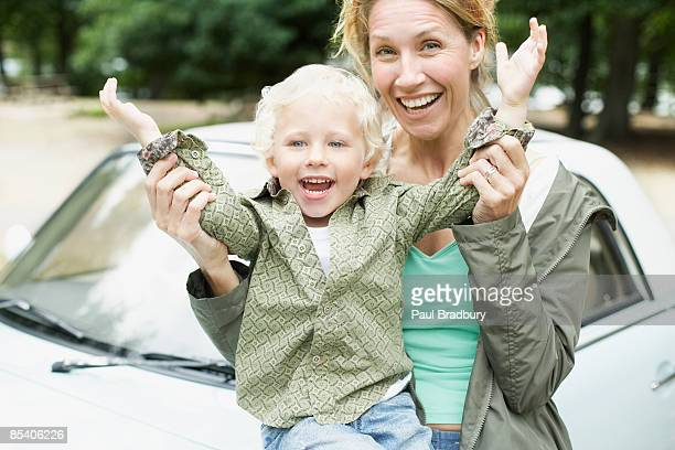 Mother and son playing near car