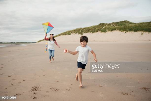 mother and son playing on the beach with a kite - kite toy stock pictures, royalty-free photos & images