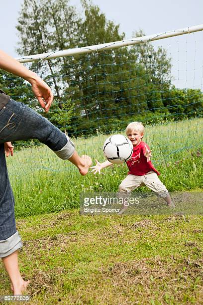 mother and son playing soccer - football bulge stock photos and pictures
