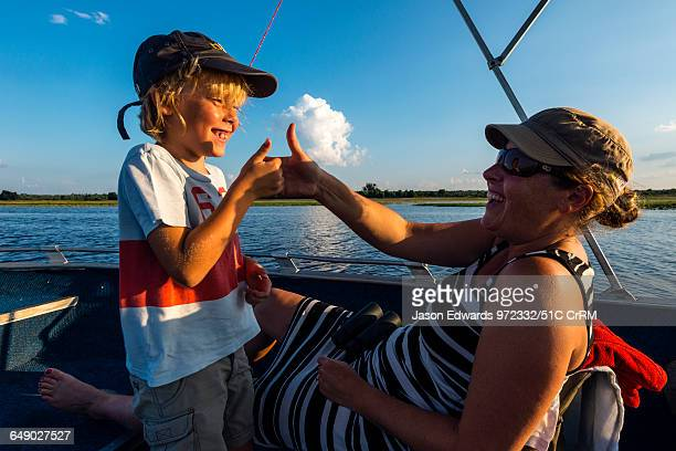 Mother and son playing thumb fighting games on an African safari boat.