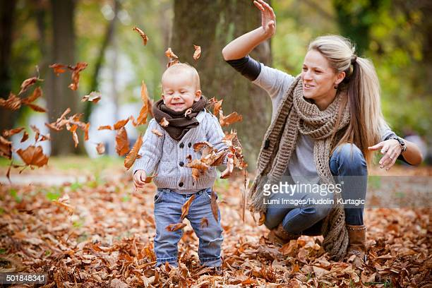 Mother and son playing together with autumn leaves, Osijek, Croatia