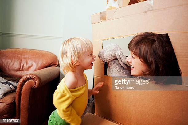 Mother and son playing with cardboard box window in living room