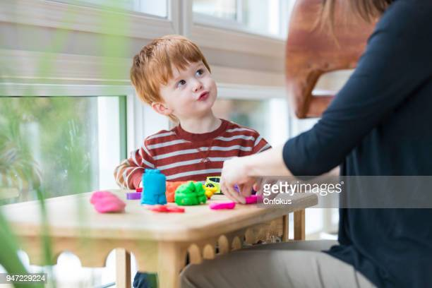 mother and son playing with child's play clay at home - clay stock pictures, royalty-free photos & images
