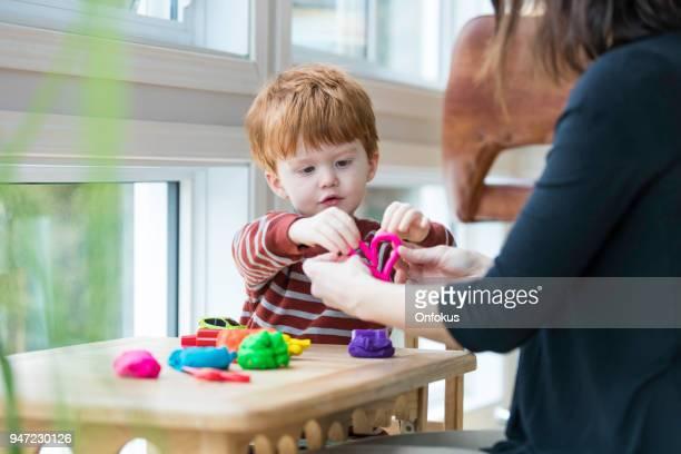 mutter und sohn spielt mit lehm zu hause zum kinderspiel - muttertag herz stock-fotos und bilder