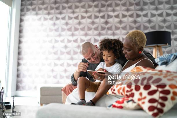 mother and son playing with digital tablet - brazilian ethnicity stock pictures, royalty-free photos & images