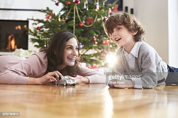 Mother and son (7-9) playing with toy car by Christmas tree