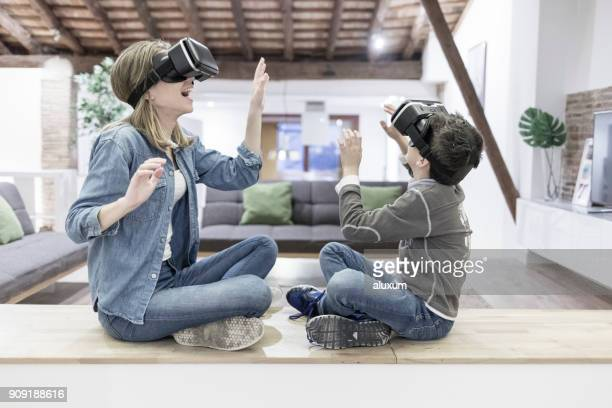 mother and son playing with virtual reality glasses in living room - 3d mom son stock photos and pictures