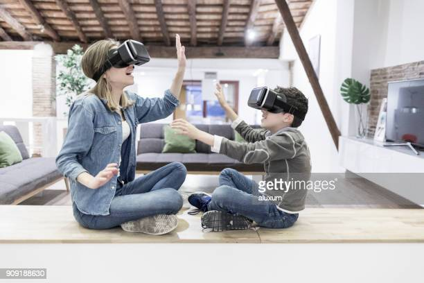 Mother and son playing with virtual reality glasses in living room