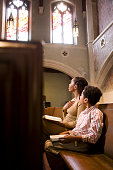 Mother and Son Praying from Bible in Church