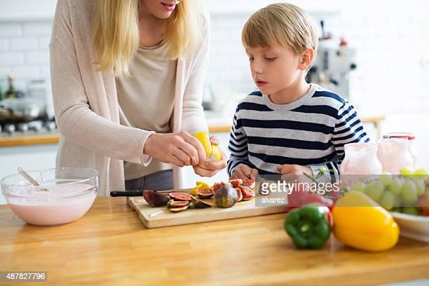 Mère et fils dans la cuisine à préparer la nourriture