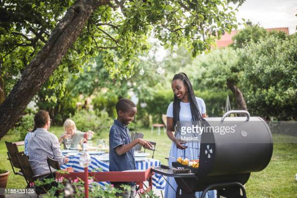 mother and son preparing food on barbecue grill in yard during weekend party - 網焼き ストックフォトと画像