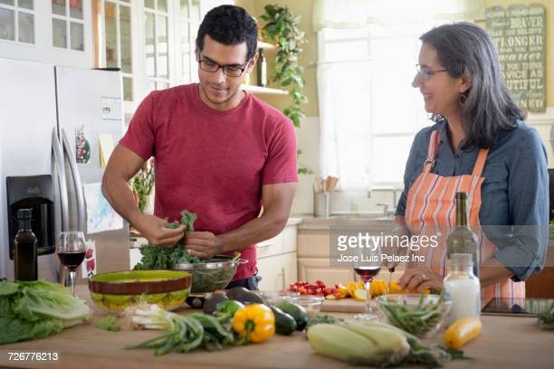 Mother and son preparing salad in domestic kitchen
