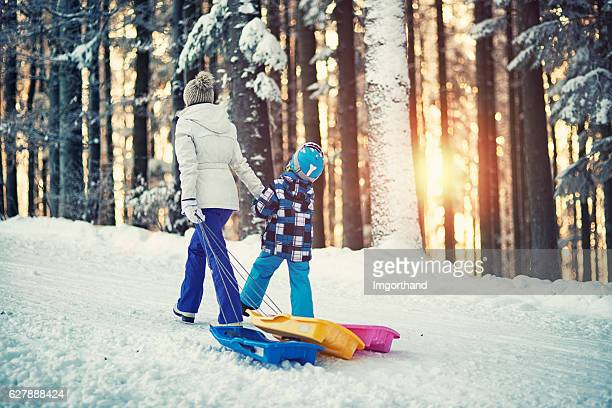 Mother and son pulling sleds in winter forest.