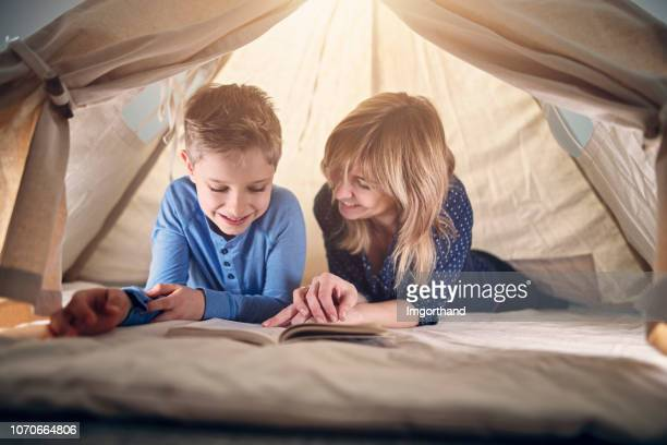 mother and son reading a book in teepee tent - teepee stock pictures, royalty-free photos & images