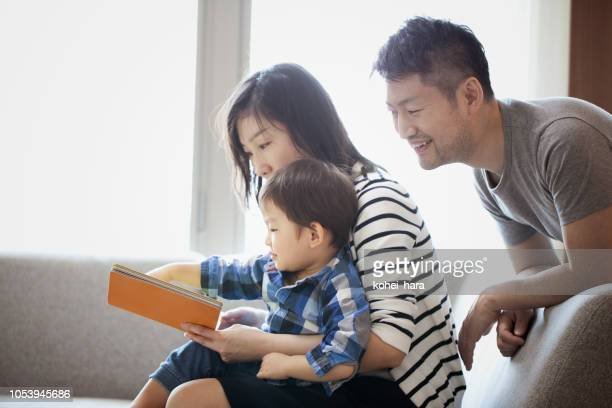 mother and son reading a book together and father watching it - japan mom and son stock photos and pictures