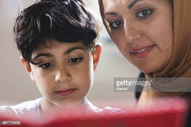 Mother and son reading book at home