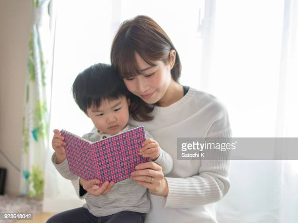 mother and son reading book in living room - japan mom and son stock photos and pictures