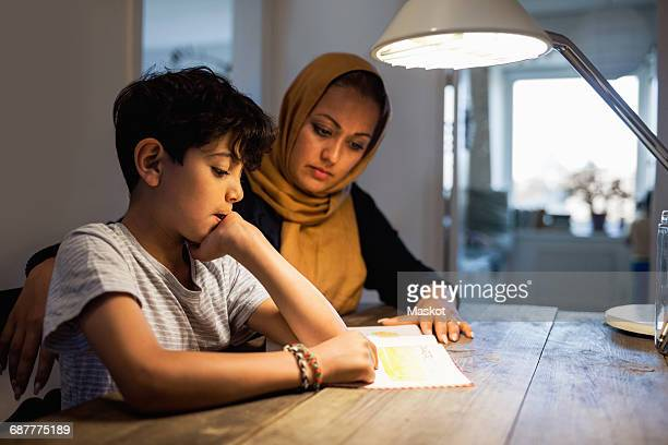 Mother and son reading book under illuminated desk lamp at home