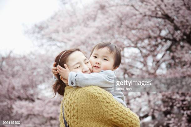 mother and son relaxed in front of cherry trees - hanami stock pictures, royalty-free photos & images