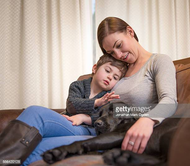 Mother and son relaxing on sofa at home with pet labrador