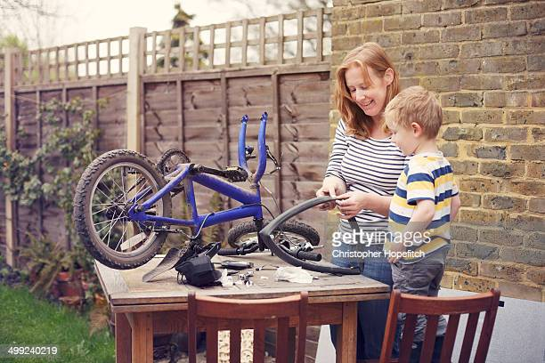 Mother and son repairing bicycle tyre puncture