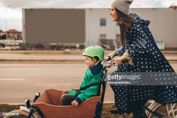 mother and son riding a cargo bike - mother son shower stock photos and pictures