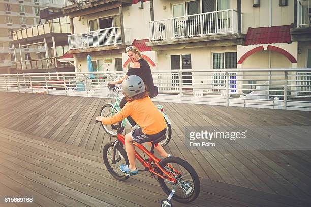 Mother and son riding bicycles on the boardwalk.