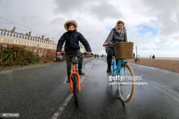 mother and son riding bicycles - mother son shower stock photos and pictures