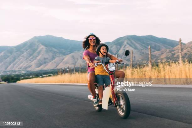 mère et fils conduisant sur le scooter rétro - mobylette photos et images de collection