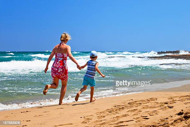 Mother and son running along sandy beach