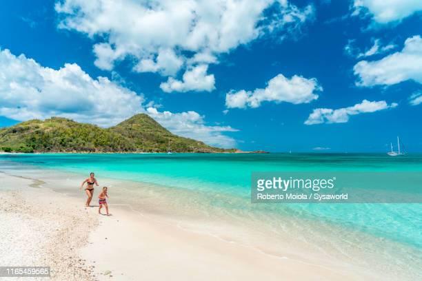 mother and son running on beach, caribbean - islas mauricio fotografías e imágenes de stock
