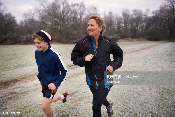 mother and son running on frosty grassland looking away smiling - son stock pictures, royalty-free photos & images