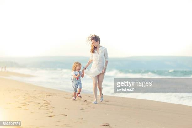 Mother and son running on the beach