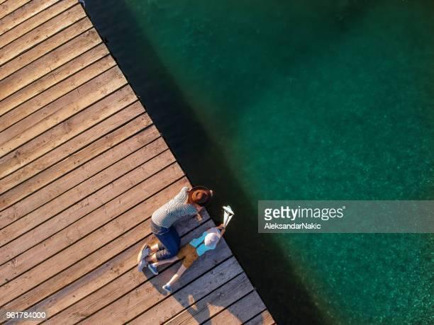 moeder en zoon zeilen zijn speelgoed boot - pier stockfoto's en -beelden