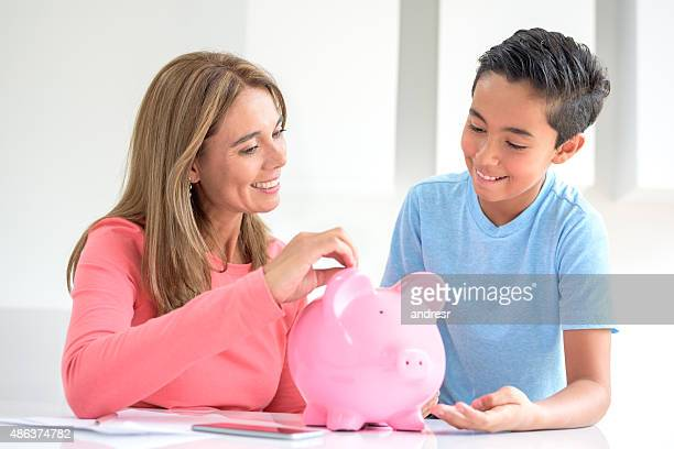 Mother and son saving money in a piggybank