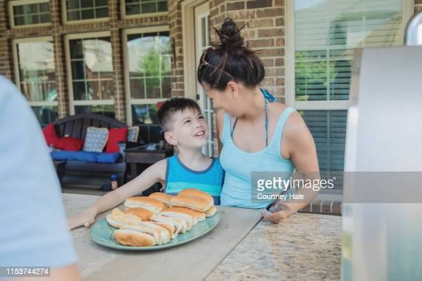 mother and son serving food to neighbors together during cookout - filipino family dinner stock pictures, royalty-free photos & images