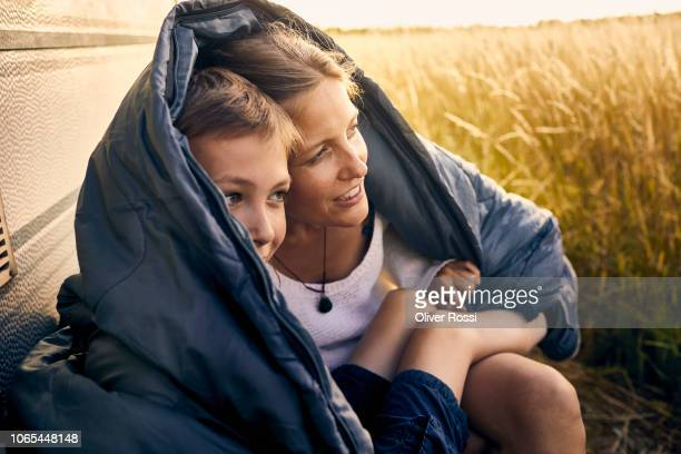 mother and son sharing a sleeping bag at a caravan - protezione foto e immagini stock
