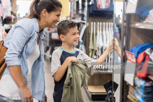 a mother and son shop for new clothes after school - back to school stock pictures, royalty-free photos & images