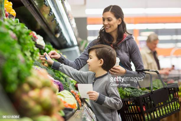 mother and son shopping for vegetables at supermarket - groceries stock pictures, royalty-free photos & images