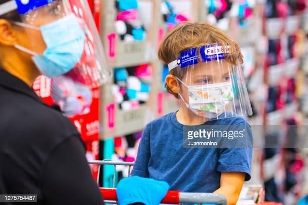 保護フェイスマスクとフェイスシールドを身に着けたメガストアでの母と息子の買い物 - フェイスシールド ストックフォトと画像
