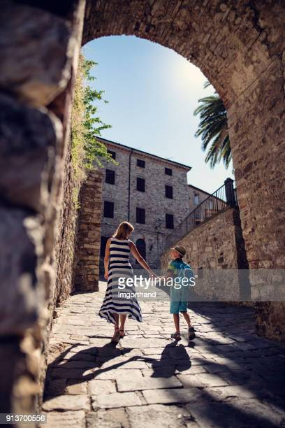 Mother and son sightseeing small italian town