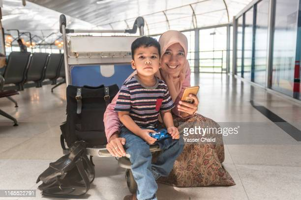 mother and son sit at trolley airport - toddler at airport stock pictures, royalty-free photos & images